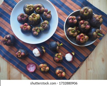 Mangosteens is queen of fruit, As known the purple mangosteen, A tropical evergreen tree with edible fruit native to island nation of Southeast Asia. Fresh ripe fruits on loincloth and wooden table.