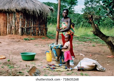 MANGUE, ANGOLA - May 15, 2007: A mother with her two children prepares Manjok to have something to eat.