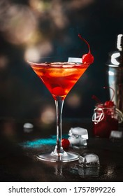 Manhattan alcoholic cocktail with bourbon, red vemuth, bitter, ice and cocktail cherry in glass, night mood image, copy space