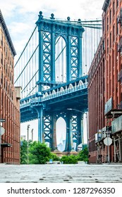 Manhattan Bridge between Manhattan and Brooklyn over East River seen from a narrow alley enclosed by two brick buildings on a sunny day in Washington street in Dumbo, Brooklyn, NYC