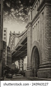 The Manhattan Bridge between buildings, Brooklyn. Street view at sunset.