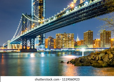 Manhattan Bridge by night, viewed from Brooklyn Bridge park, in New York City