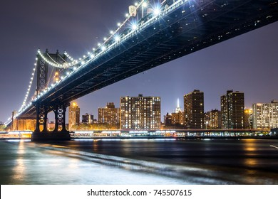 Manhattan bridge at night with Empire State Building in the background
