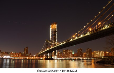 Manhattan Bridge at night as seen from Brooklyn Bridge Park in New York City.