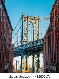 Manhattan bridge in old narrow Brooklyn street in perspective, New York, USA. Business and travel background.