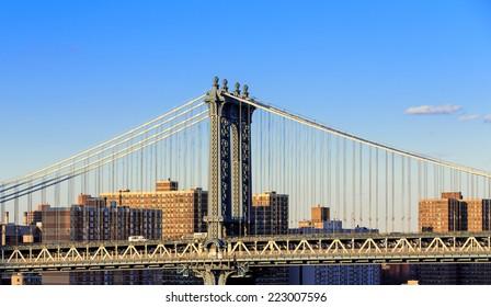 Manhattan Bridge over East River viewed from New York City Lower Manhattan waterfront at sunset.