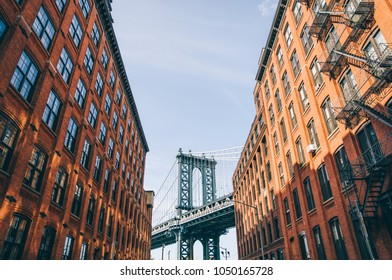Manhattan bridge seen from a red brick buildings in Brooklyn street in perspective, New York, USA