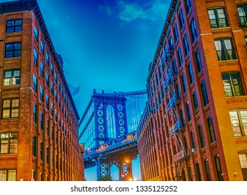 The Manhattan Bridge at sunset framed by Brooklyn buildings - NYC, USA.