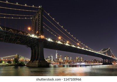Manhattan and Brooklyn bridges with New York City skyline at night, USA