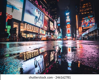 Manhattan, circa oct 2014: Typical Time square night view scenery in New york city. Taxi, lights and tourist are reflected in a  water puddle
