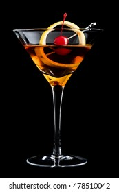 Manhattan cocktail with lemon and maraschino cherry on black background