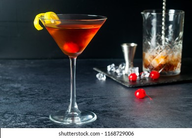 Manhattan Cocktail With Maraschino Cherry, Ice, Lemon Twist And Decanter On Dark Background
