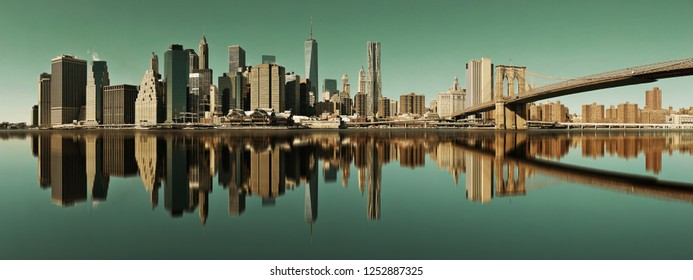 Manhattan financial district with skyscrapers and Brooklyn Bridge with reflections.