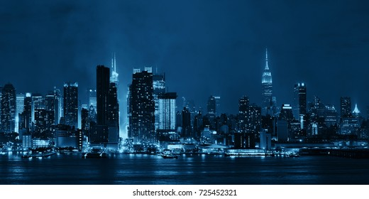 Manhattan midtown skyscrapers and New York City skyline panorama at night with fog