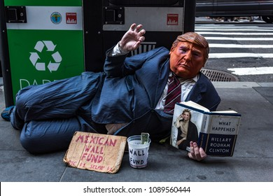 MANHATTAN, NEW YORK - 03 MAY, 2018: Person with a president Trump costume reading a book from Hillary Rodham Clinton.
