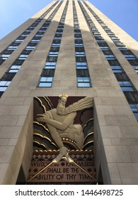 Manhattan, New York / America, USA - april 2019 : Low angle view over the Comcast Building skyscraper and its famous sculpture and quote, starting by wisdom and knowledge, Rockefeller Center, Nyc.