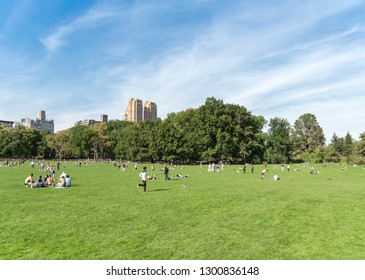 Manhattan, New York circa summer 2018 many people in Central Park enjoying the warm weather playing on the green grass.