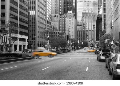 Manhattan, New York city in early morning with almost no traffic on the street between many skycrapers with yellow caps motion blurred in black and white composition