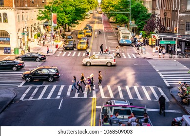 Manhattan, New York City - June 14, 2017: NYC intersection crowded with busy people, cars and yellow taxis. Iconic traffic and daily street business with urban look and pedestrian crossings.