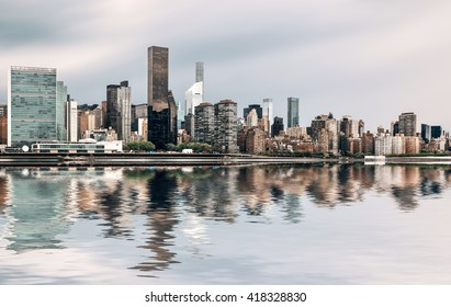 Manhattan, New York City. Panoramic view of Midtown skyline across the East River on an overcast day with water reflection