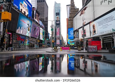 Manhattan, New York City, USA - February 16, 2021. Bright advertisement screens on Times Square reflected in puddle. Big day city lights, reflection photography concept