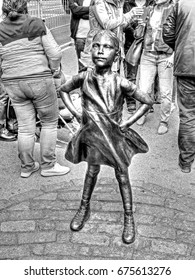 """MANHATTAN, NEW YORK CITY/USA - APRIL 14, 2017: A bronze statue entitled """"Fearless Girl"""" by sculptor Kristen Visbal which was officially unveiled in Lower Manhattan, opposite the Wall Street Bull."""