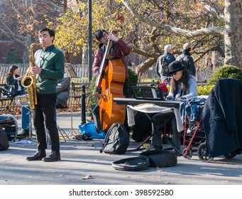 Manhattan, New York - December 06 2015: Team of street musicians playing during lazy Sunday afternoon in Washington Square Park.