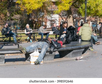 Manhattan, New York - December 06 2015: People sitting and laying on the benches  during lazy Sunday afternoon in Washington Square Park.