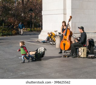 Manhattan, New York - December 06 2015: Child left some money to street musicians playing during lazy Sunday afternoon in Washington Square Park.