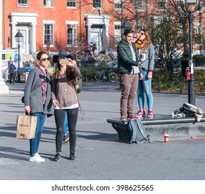 Manhattan, New York - December 06 2015: People making selfies during lazy Sunday afternoon in Washington Square Park.