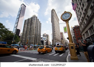 Manhattan, New York, June, 2017: taxis on the road and the golden clock in front of Flatiron building