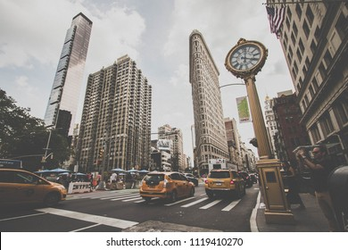 Manhattan, New York, June, 2017: traffic at 5th Avenue, Golden clock and Flatiron building in vintage style