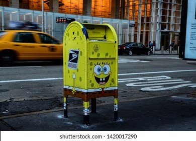 Manhattan, New York, NY, USA - June 20, 2015: United States Postal Service (USPS) Mailbox on Sixth Avenue is painted like Spongebob squarepants, with yellow taxi cab passing behind it