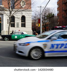 Manhattan, New York, NY / USA - February 2019: Modern New York Police Department (NYPD) car is passing by a classic old historic police car in Manhattan, NY, USA