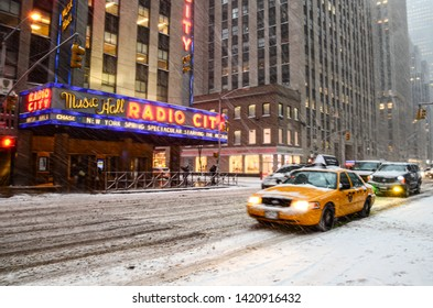 Manhattan, New York, NY, USA - December 1, 2018: Yellow New York City Taxi Cab riding through snow covered streets of Manhattan during the snowstorm