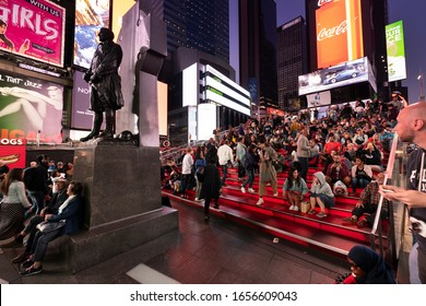 Manhattan, New York - September 18, 2019:  People gather by the George M. Cohan Statue in front of the digital advertising and brightly lit billboards of Broadway in Times Square New York City USA