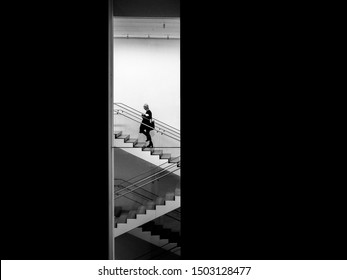 Manhattan, New York, United States of America - Jan 23 2015: The staff going up stairs in a hurry in Musuem of Modern Art, or MoMA, one of the largest and most influential museums of modern art.