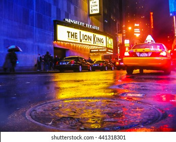 Manhattan, New York, United States - April 28th, 2008:  The Lion King, Times Square theater for Broadway shows,  city street by night with local taxi and a smoking  manhole