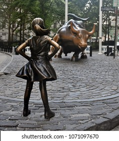 Manhattan, New York, USA - July 2, 2017: The Charging Bull and Fearless Girl statues in downtown Manhattan on Wall Street in New York City.