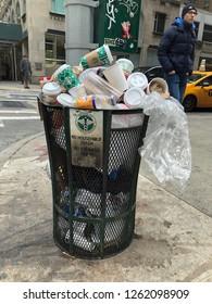 MANHATTAN, NEW YORK-DECEMBER 9, 2018:  A man walks by an overflowing garbage bin full of trash in one of Manhattan's nicest neighborhoods.