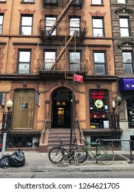MANHATTAN, NEW YORK-DECEMBER 9, 2018:  Residential street scene in midtown Manhattan.  The brownstone buildings are apartments with retail shops on the street level.