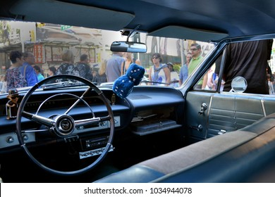 Manhattan, NY / United States - April 15, 2014: Classic vintage car blue interior with dash, steering wheel, and blue fuzzy dice.