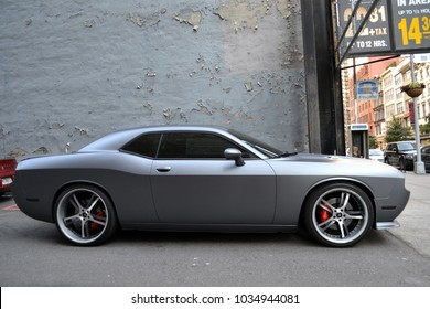 Manhattan, NY / United States - April 15, 2014: Silver Gray Dodge Challenger in New York alley in front of chipped painted wall.