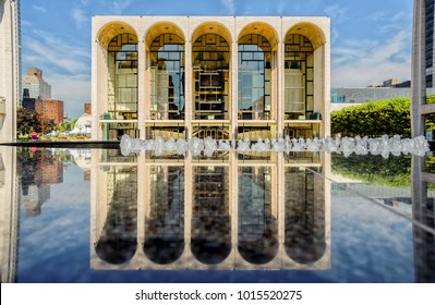 Manhattan, NYC, USA - July 12, 2014: The Metropolitan Opera House reflected on the marble fountain of the Lincoln Square.