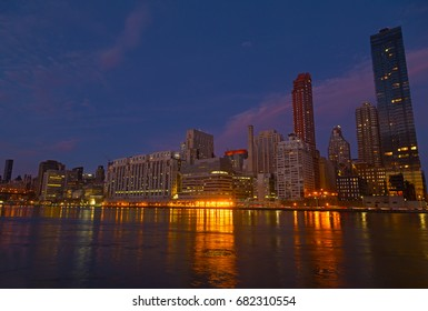 Manhattan panorama at dusk as seen from Roosevelt Island in New York, USA. New York night scene with East River waterfront illuminated buildings.