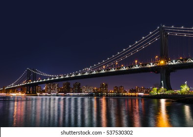 Manhattan Skyline and Manhattan Bridge at night with reflections in East River. Manhattan Bridge is a suspension bridge that crosses the East River in New York City