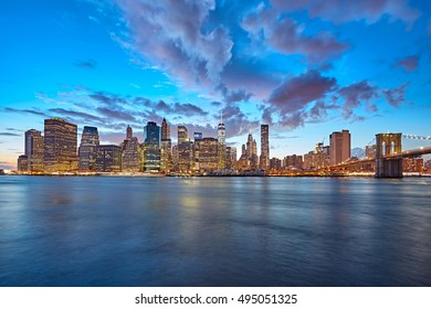 The Manhattan skyline and Brooklyn Bridge as seen from across the East River at dusk. New York City at night.
