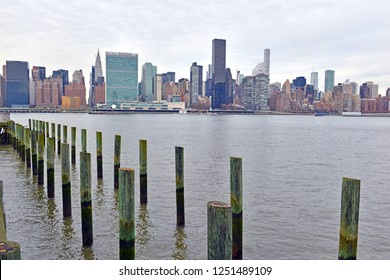 Manhattan skyline cityscape with wooden pier, on East side with commercial buildings and residential high rise apartment real estate