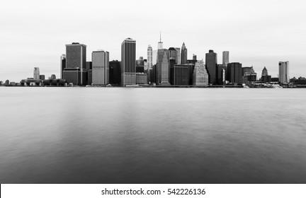 Manhattan Skyline am bewölkten Tag, New Yorker Wolkenkratzer im Wasser, Schwarz-Weiß-Foto, USA