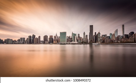 Manhattan Skyline during an incredible sunset. Photo taken from Gantry Park, Queens. The Sun was setting in a way that left half the skyline a dark purple gray color, and the other half orange.